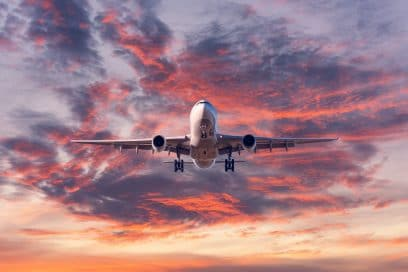 Landing airplane. Landscape with passenger airplane is flying in the blue sky with red, purple and orange clouds at sunset. Travel background. Passenger plane. Commercial aircraft. Private jet